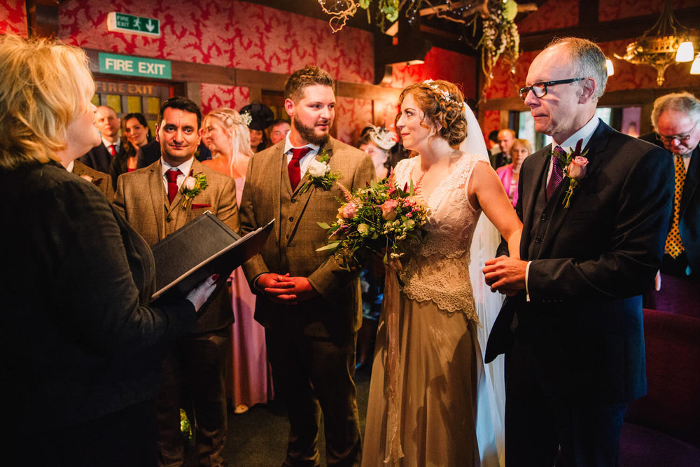 bride and groom spoken vows to registrar at top of aisle