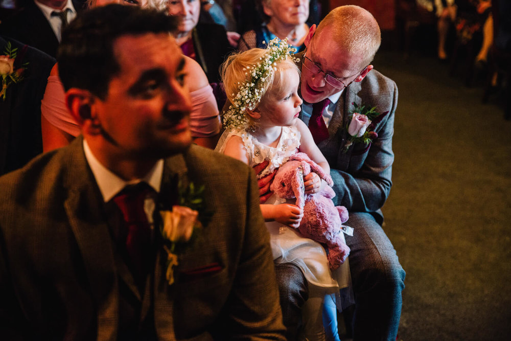 flower girl in floral tiara sat on groomsman knee during marriage service