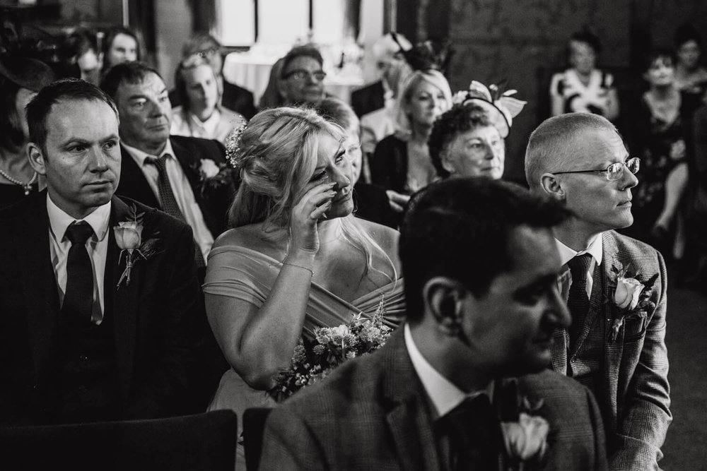 black and white photograph of bridesmaid wiping away tears