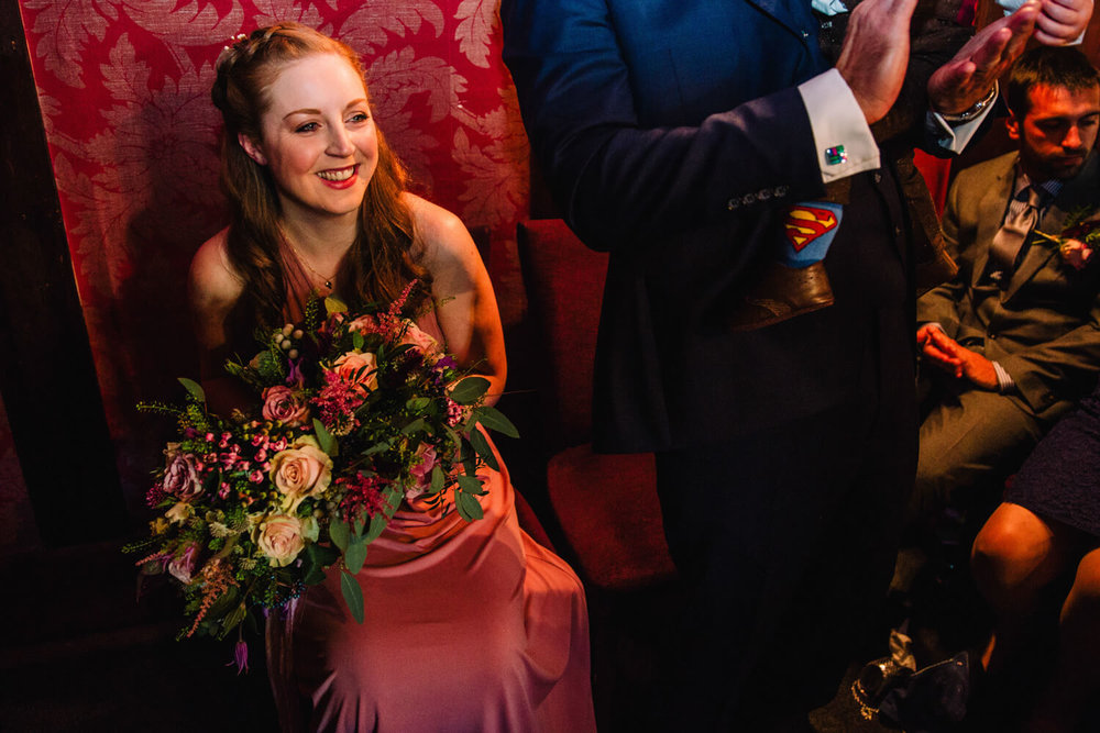 bridesmaid smiling and laughing during wedding ceremony
