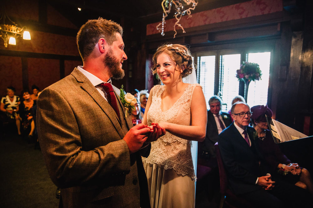 bride and groom laughing while exchanging wedding rings