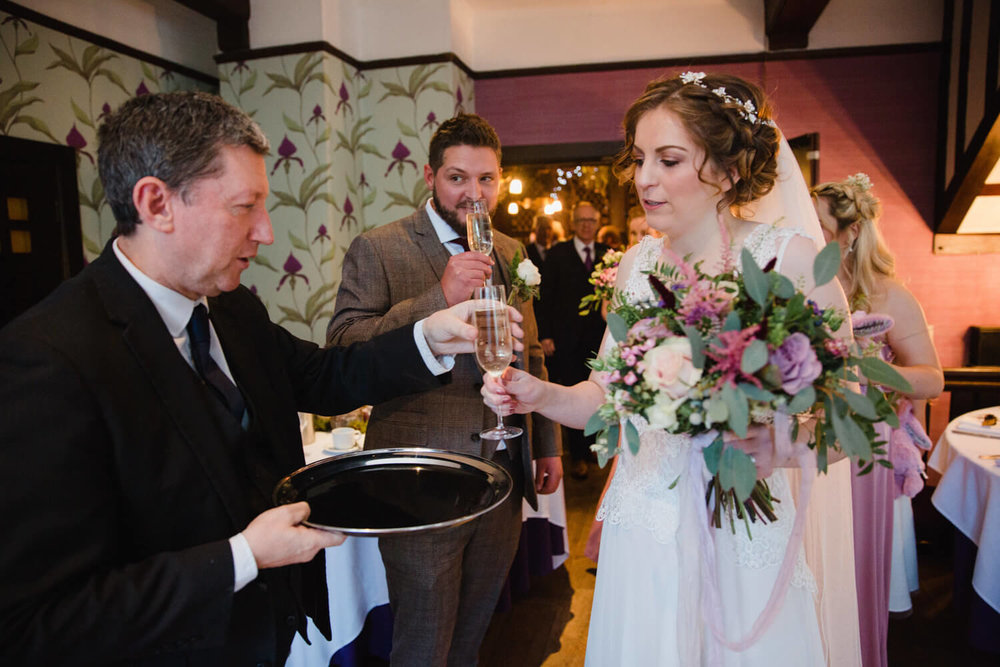 newly married couple receiving champagne flutes and congratulations