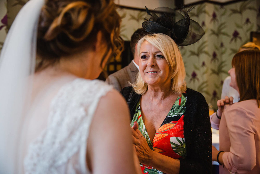 wedding guest sharing joke with bride after service