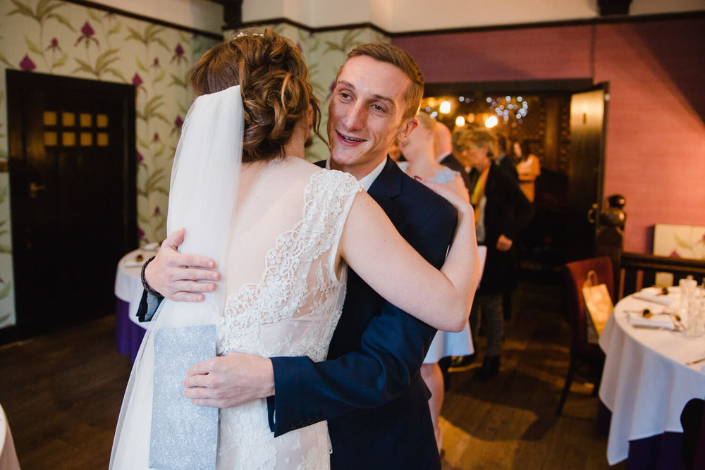 groomsman hugging and congratulating bride