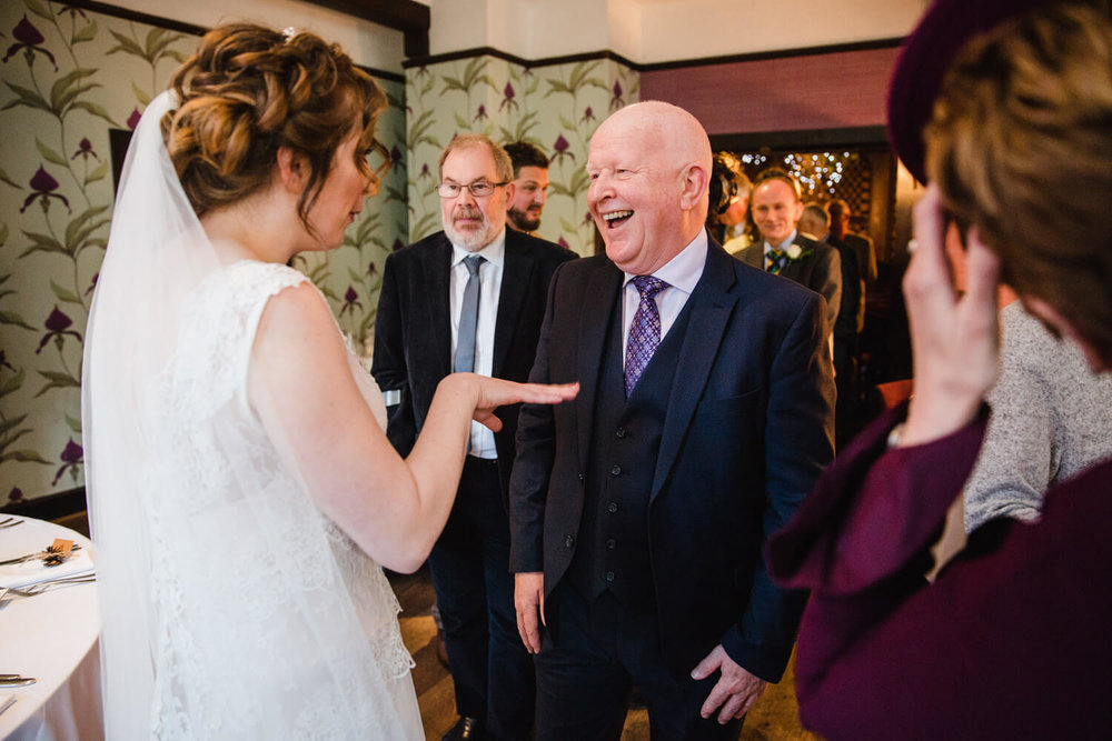 Uncle and family joking with bride after wedding