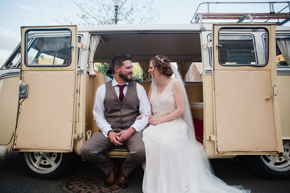 bride and groom sat on camper van step laughing and joking