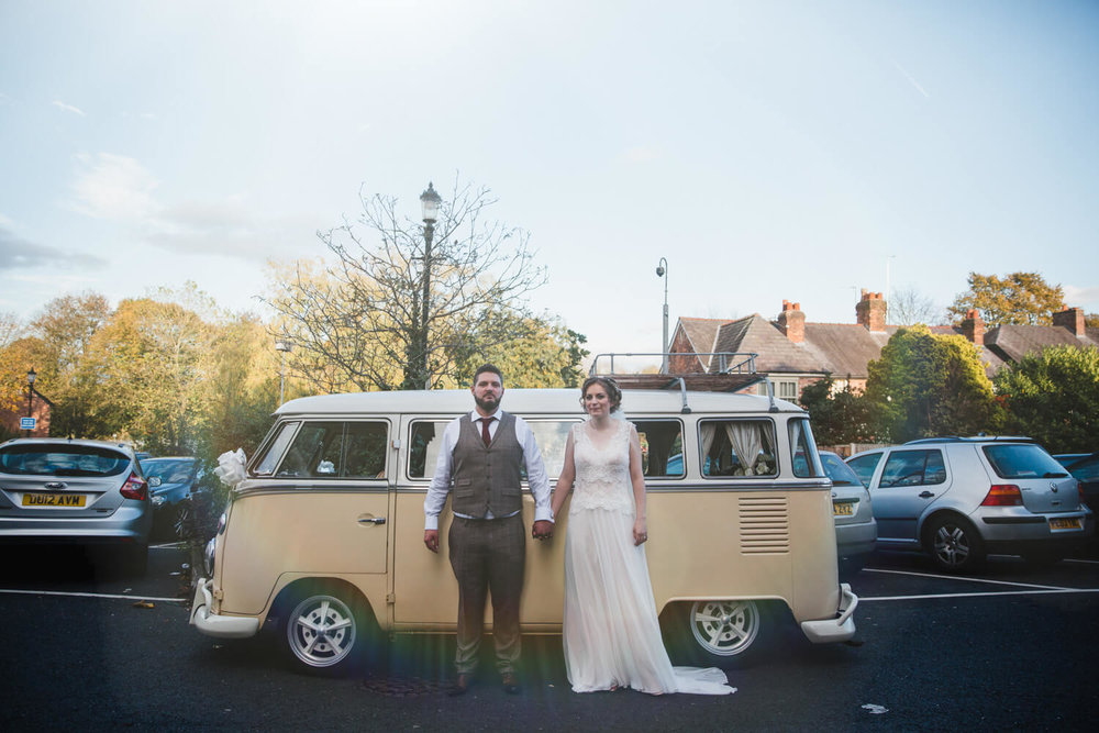 portrait of bride and groom stood in front of camper van