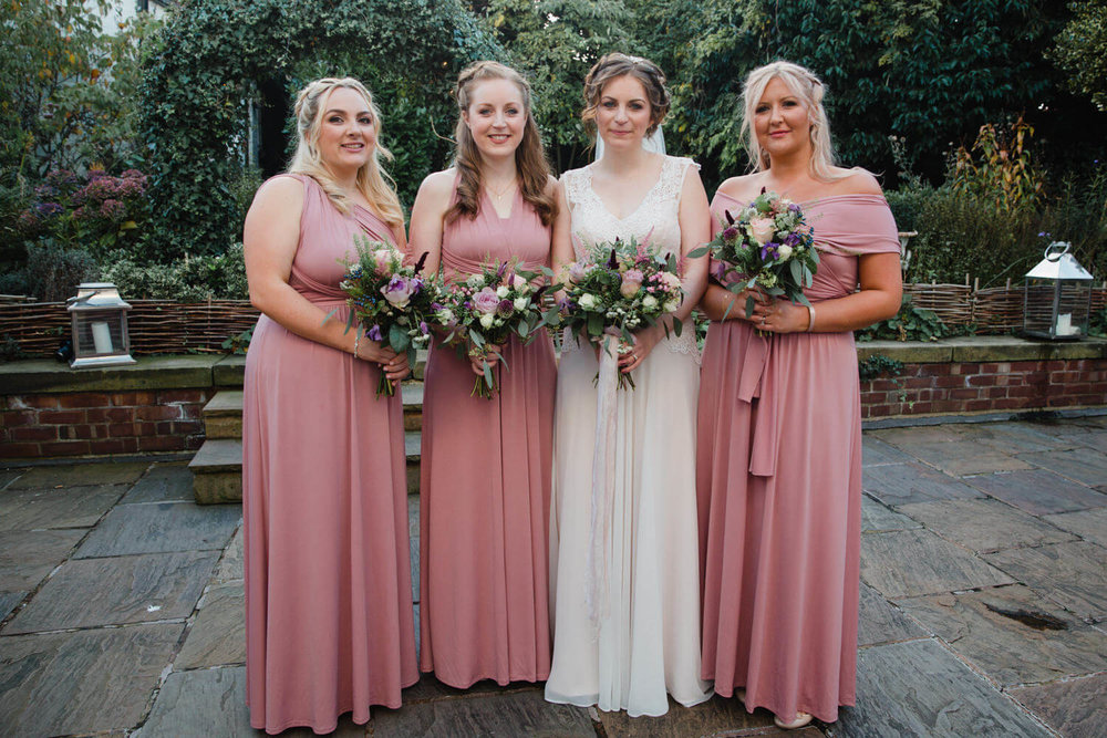 bride and bridesmaids holding bouquets for portrait