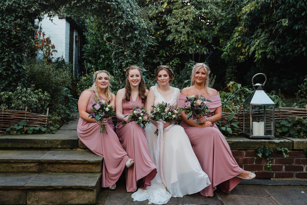 bridal party sat on wall holding bouquets