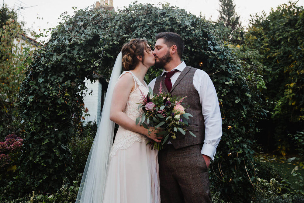 bride and groom share kiss under ivy archway