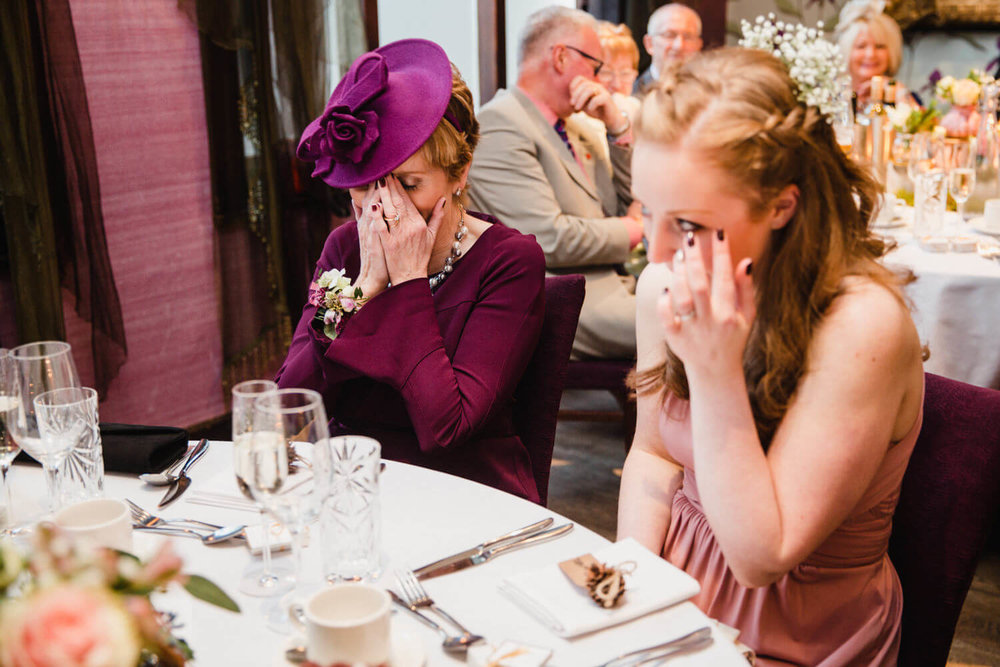 mother of bride and bridesmaid sister crying and wiping away tears