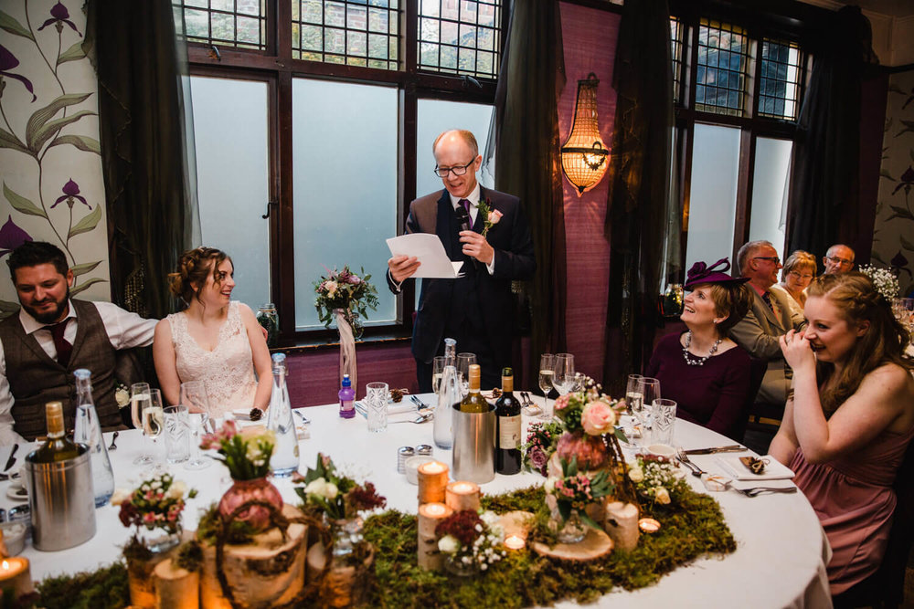 father of bride delivering speech to wedding party