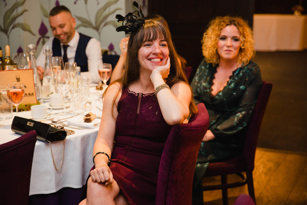wedding guest smiling during the speeches