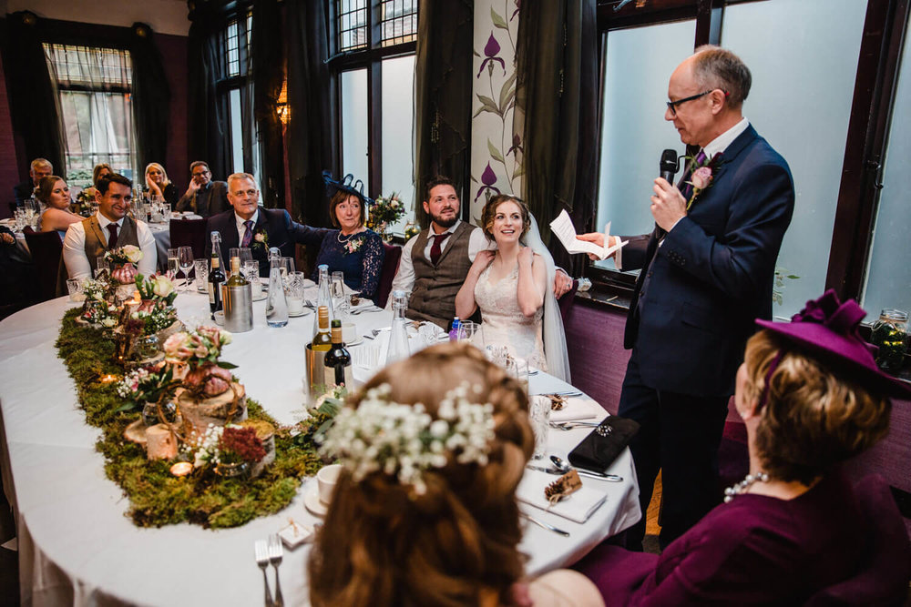 wide angle lens photograph of wedding party reacting to best man speech