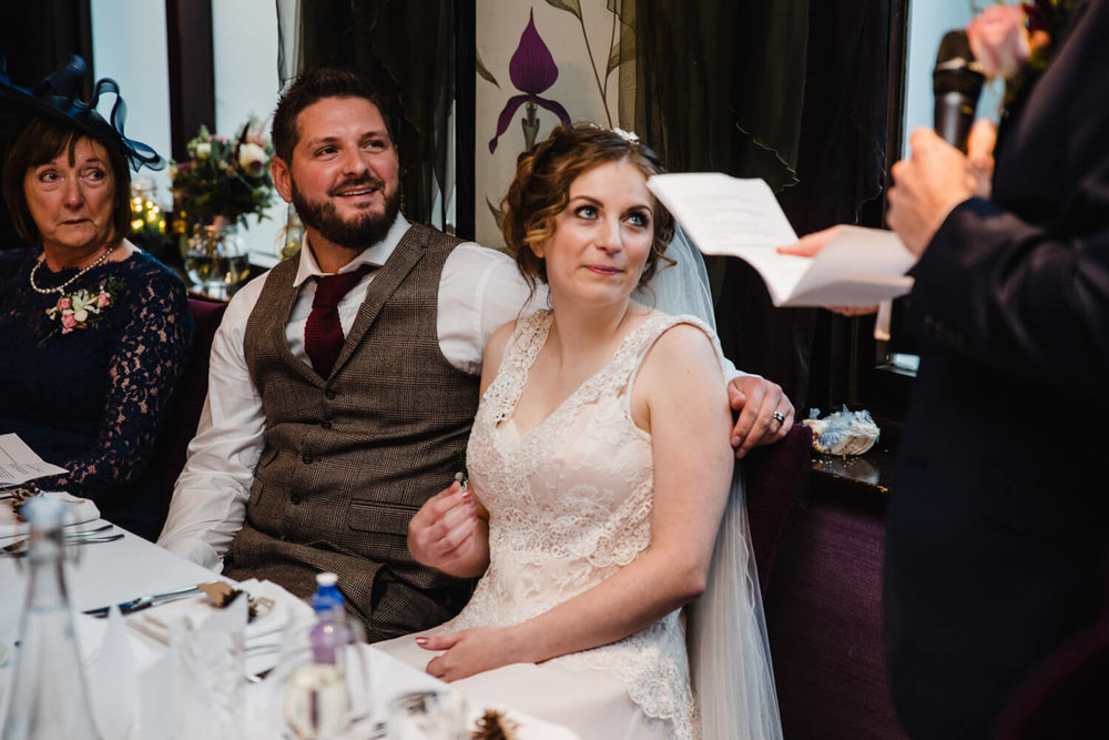 bride and groom holding hands and sharing intimate moment watching speech