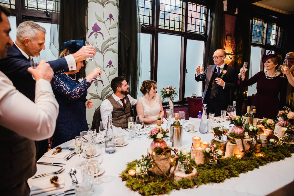 wedding party raising a toast to newlyweds
