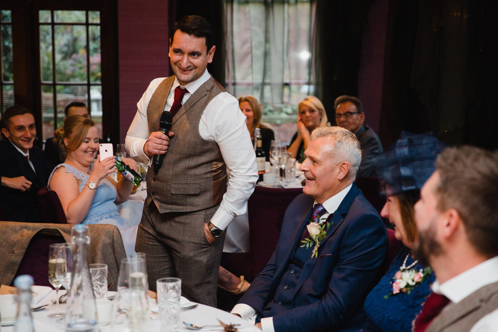 best man delivering speech to wedding couple