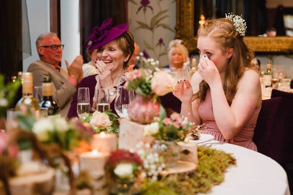 bridesmaid wiping away tears on top table
