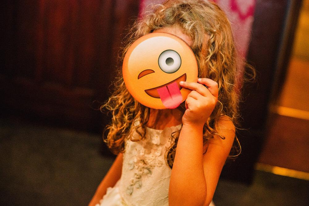 flower girl holding up emoji face