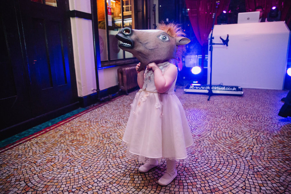 flower girl wearing horse head photo booth prop on dance floor