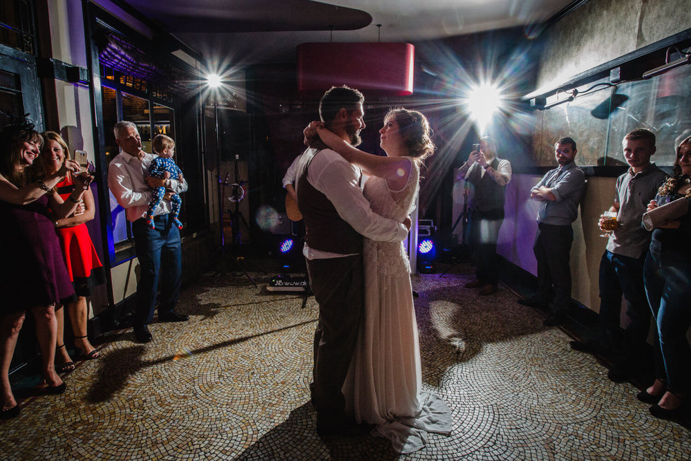 first dance of bride and groom in front of friends and family