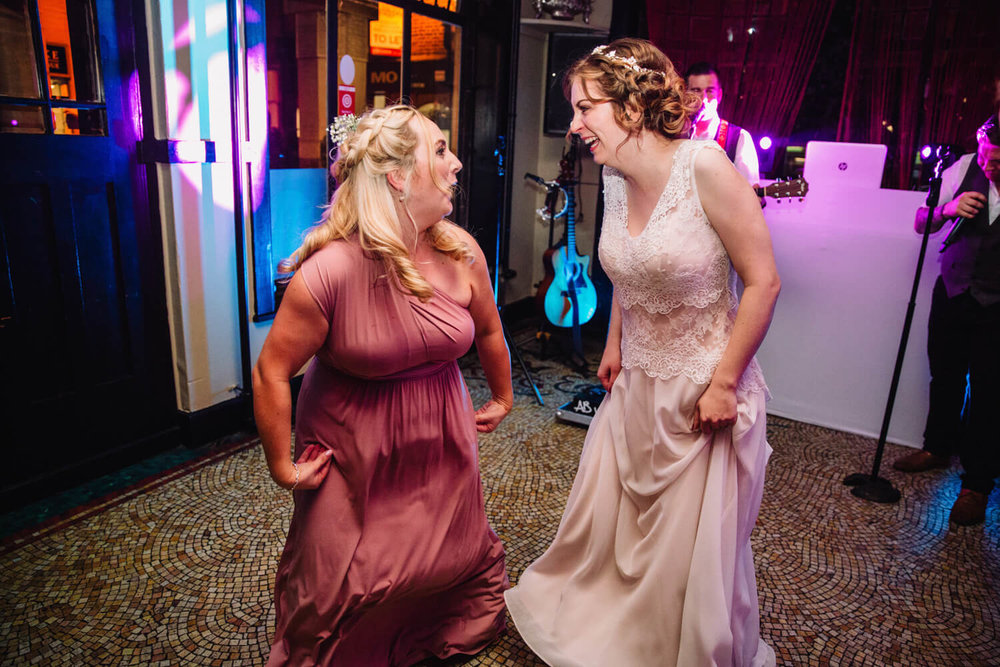 bride and bridesmaid friend laughing and joking to music