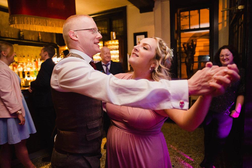 bridesmaid and groomsman dancing together