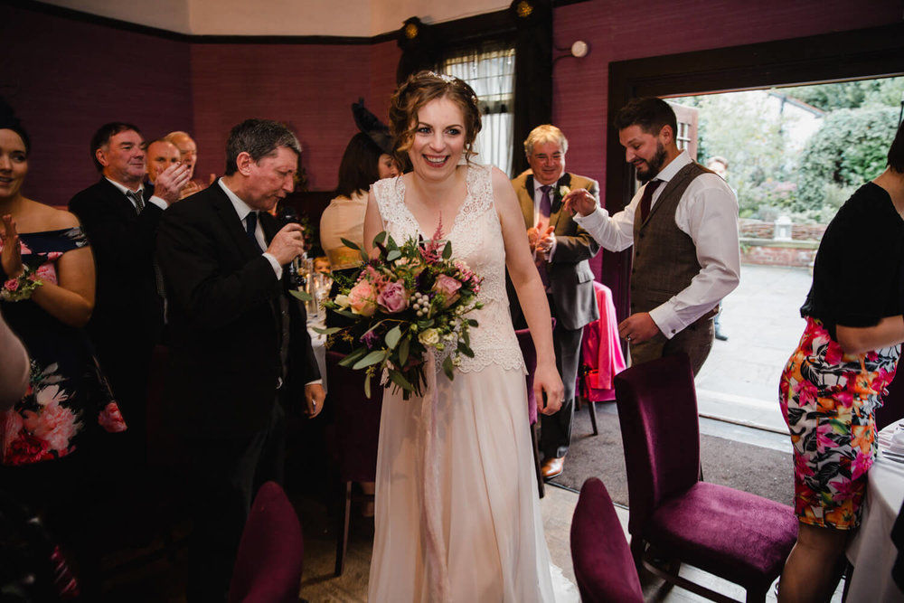 bride laughing and smiling introduced to wedding breakfast room
