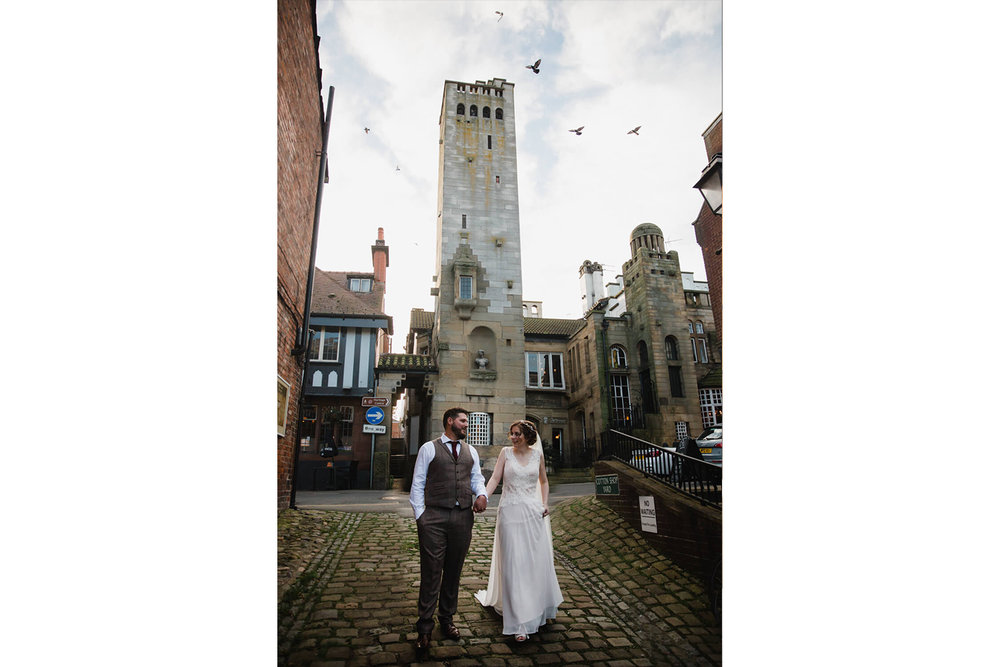 bride and groom walking down cobbled street in knutsford