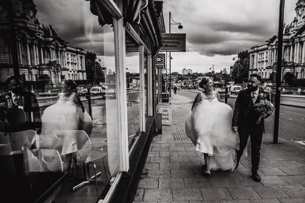 black and white photograph of bride and groom reflection in window