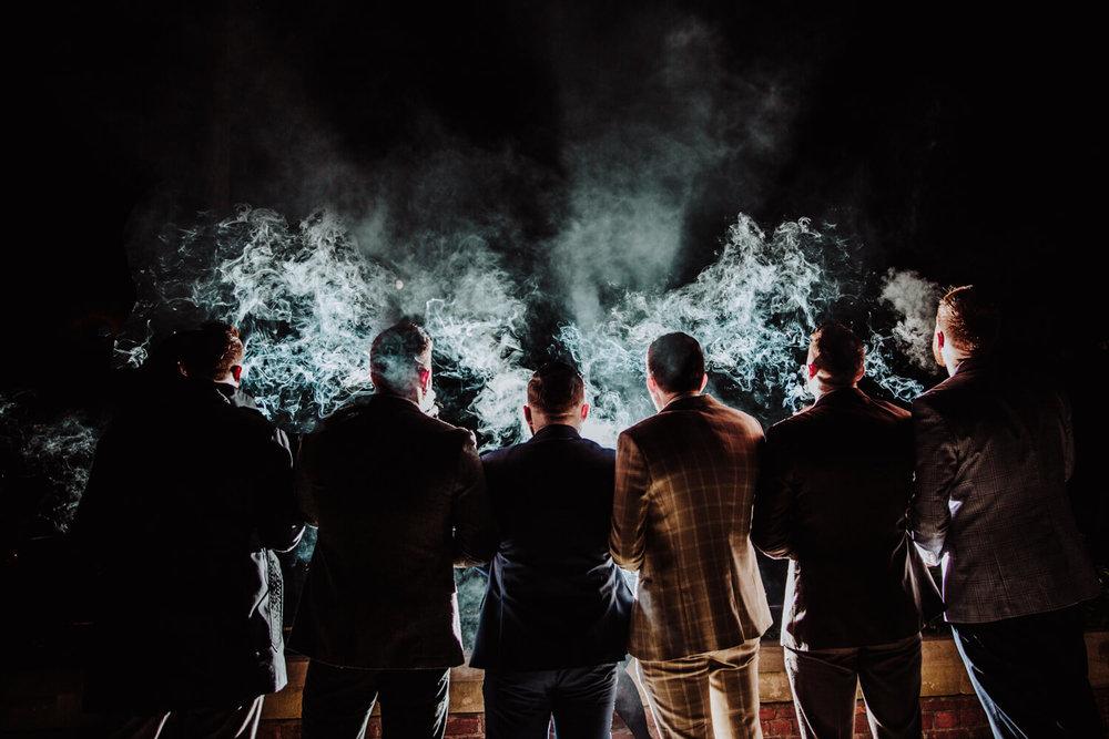 groomsmen smoking cigars in dark