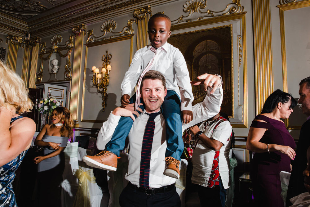 page boy on shoulders of wedding guest