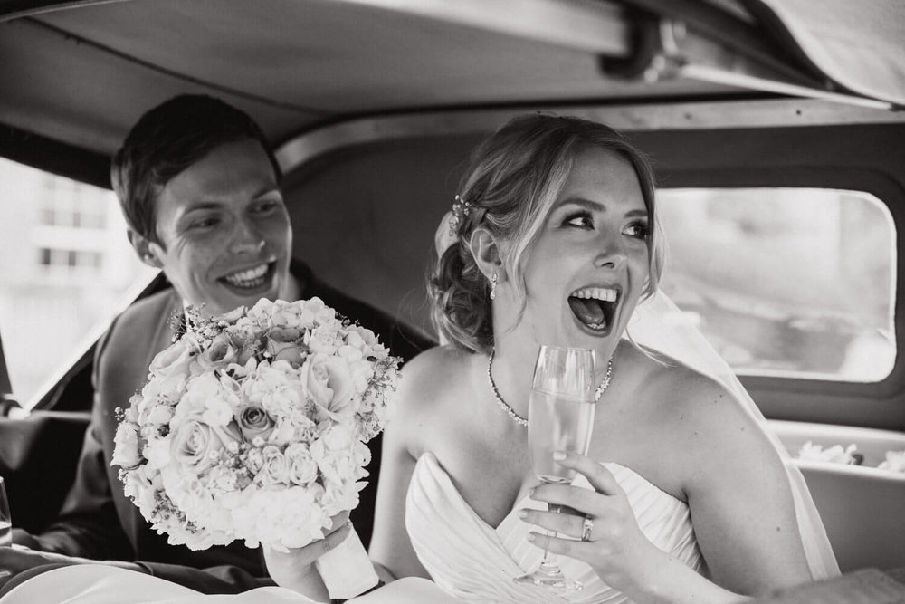 bride holding bouquet laughing with friends in wedding car