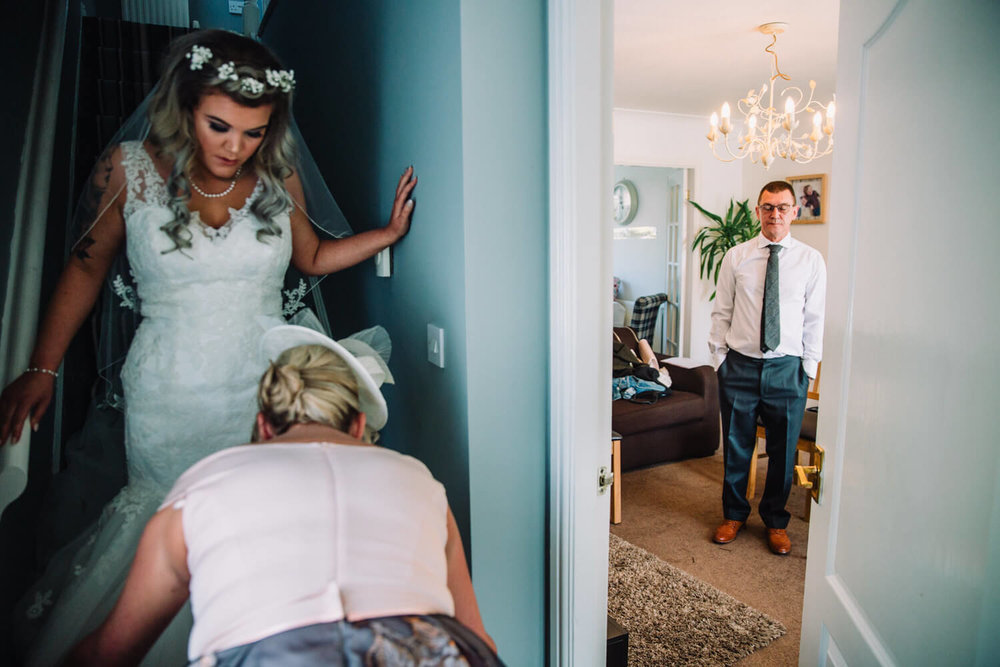bride getting ready first look with father