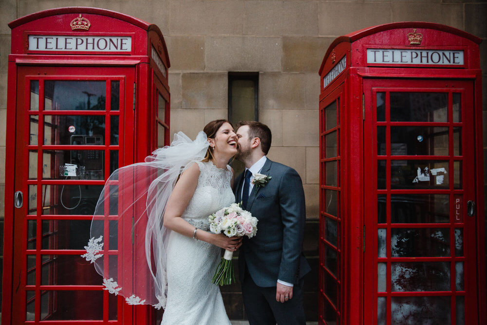 bride and groom portrait of laughing between two red telephone boxes
