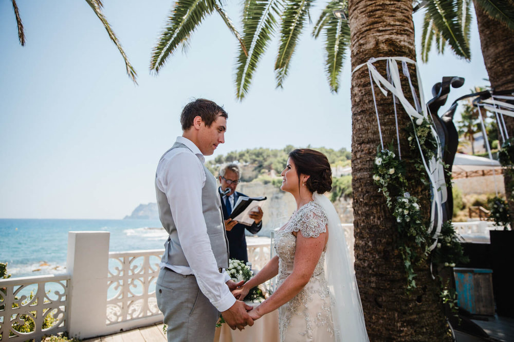 newlyweds holding hands below palm trees