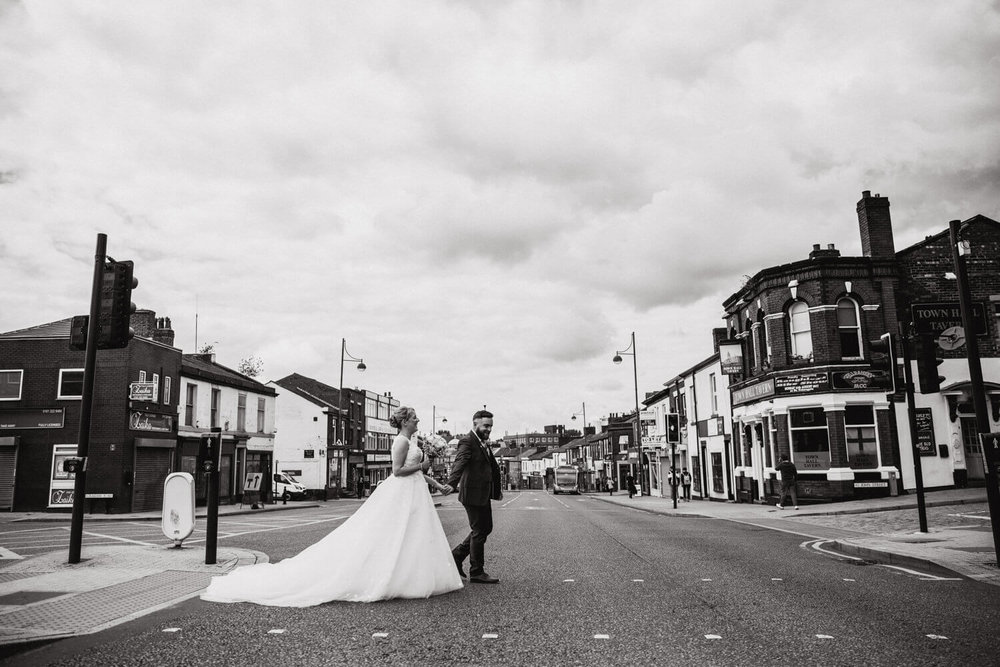bride and groom holding hands crossing road