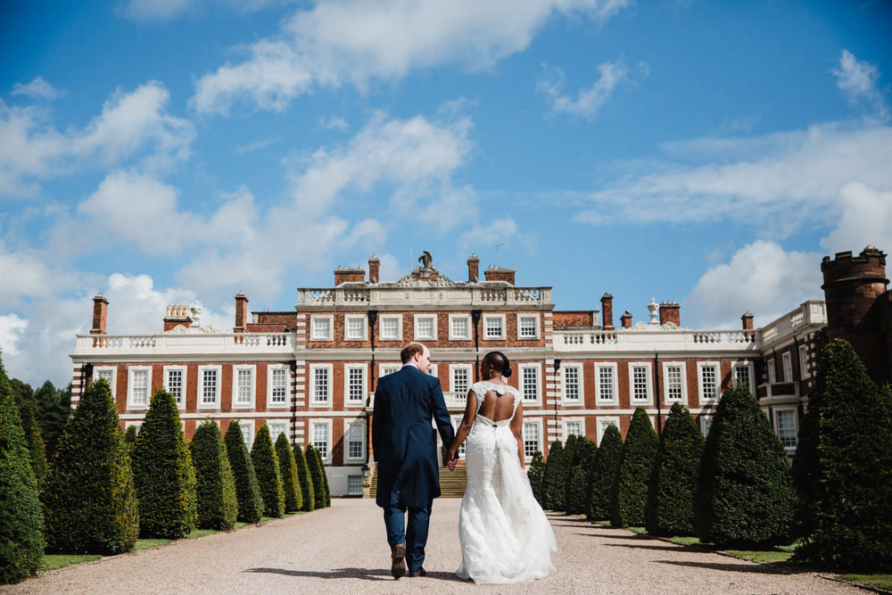 bride and groom walking up road to knowsley hall