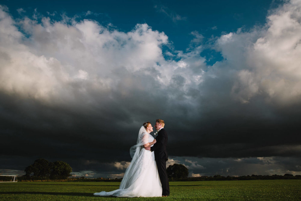 newlyweds posed under clouds in field