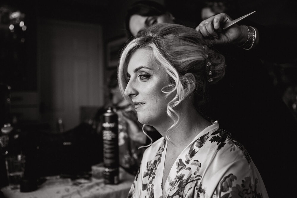 black and white photograph of bride looking out of the window during make up