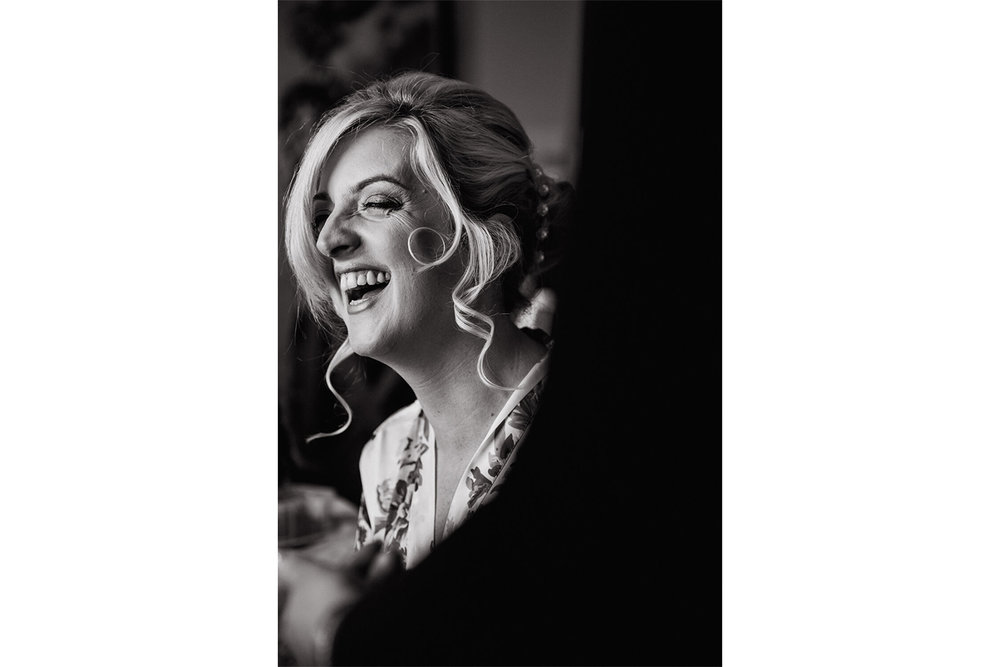black and white portrait photograph of bride laughing during make up preparation
