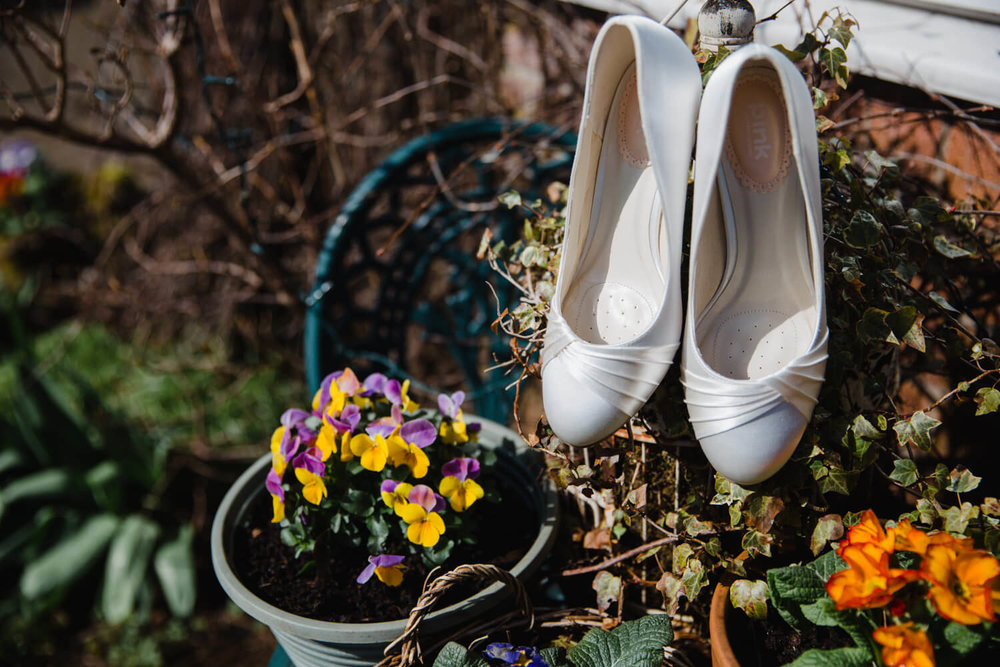 wedding shoes next to flowers in garden