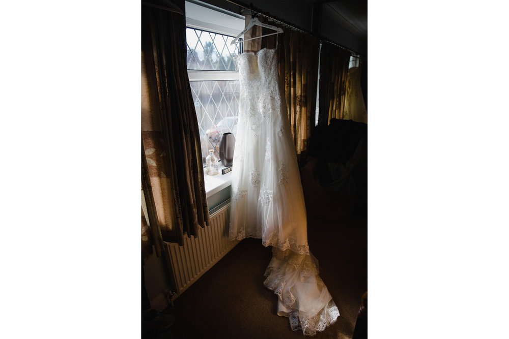 brides dress hung up on hanger in bedroom