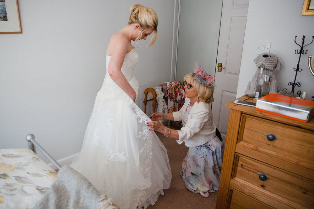 grandma helps bride in to wedding dress