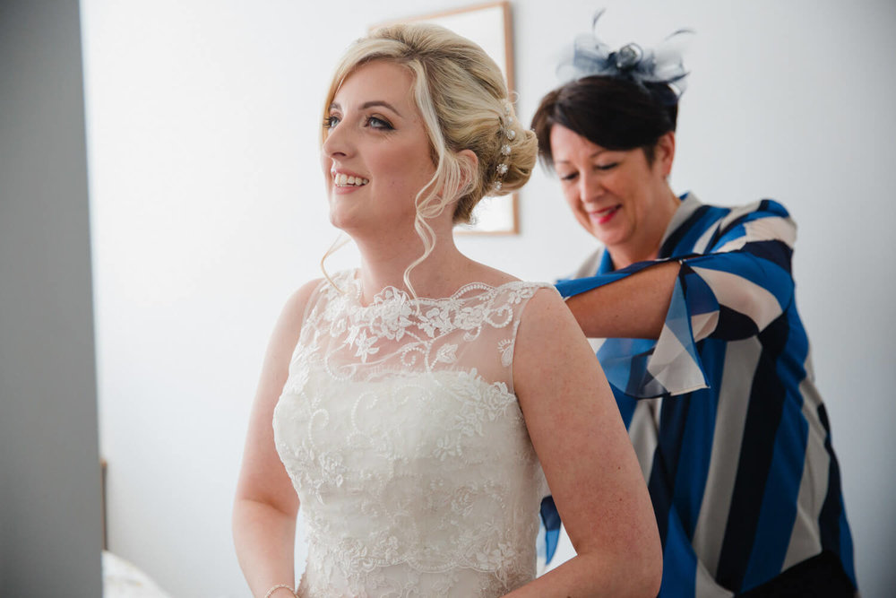 godmother helps bride to get into her wedding dress