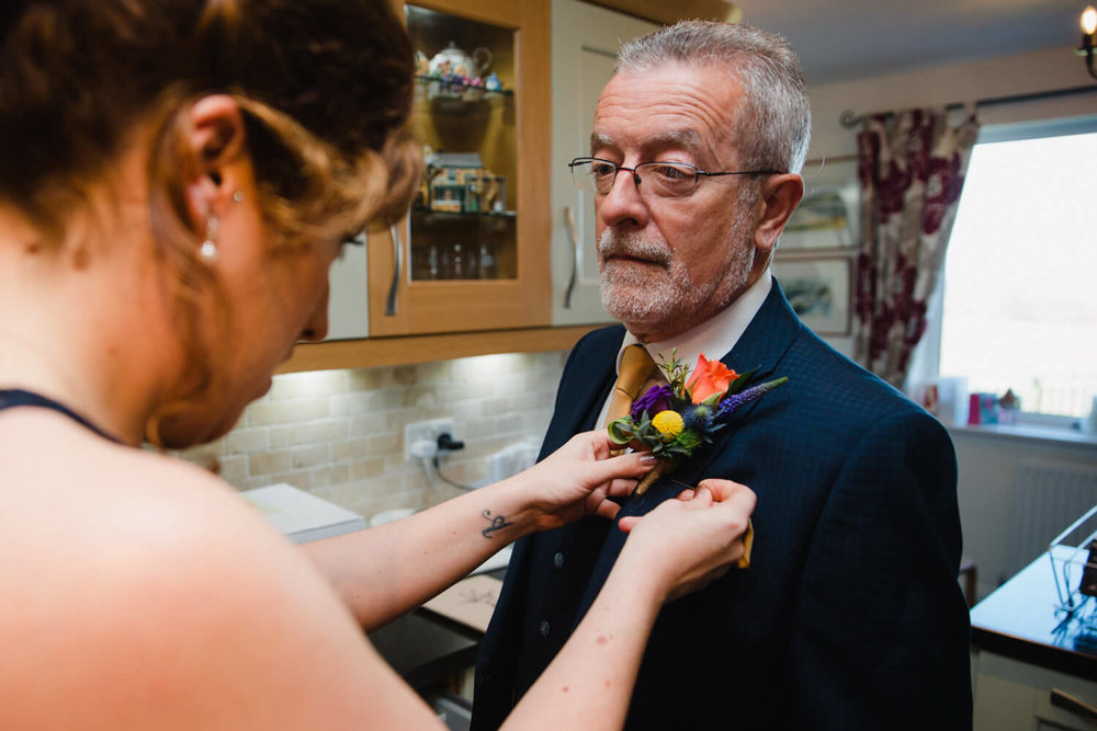 bridesmaid attaches pinhole flowers onto lapel of fathers suit