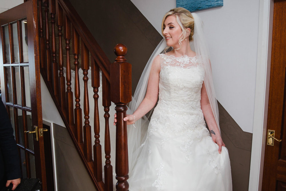 bride makes her way down stairs to be greeted by bridesmaids
