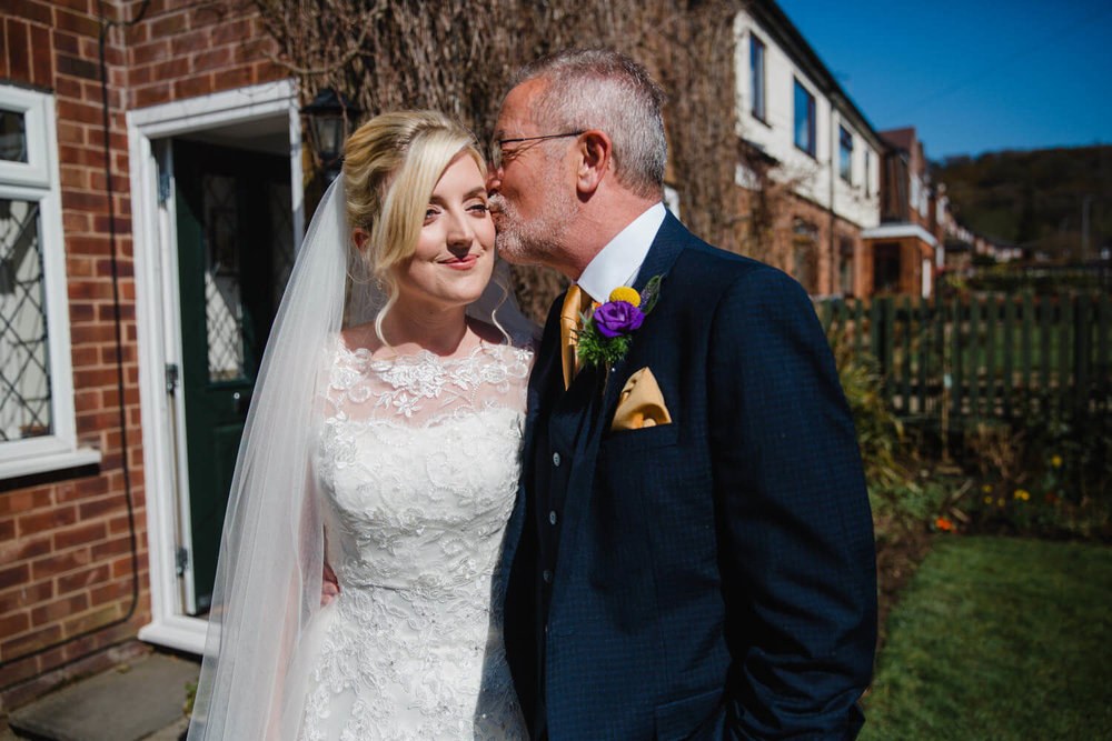 father of bride gives daughter a kiss before ceremony