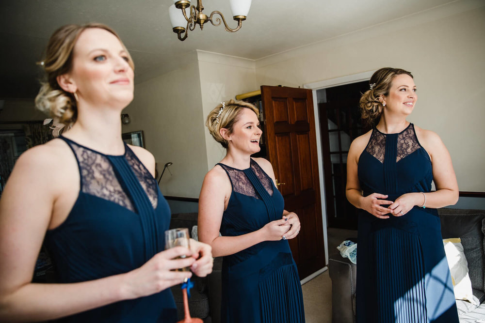 bridesmaids look out of window at bride and father first look