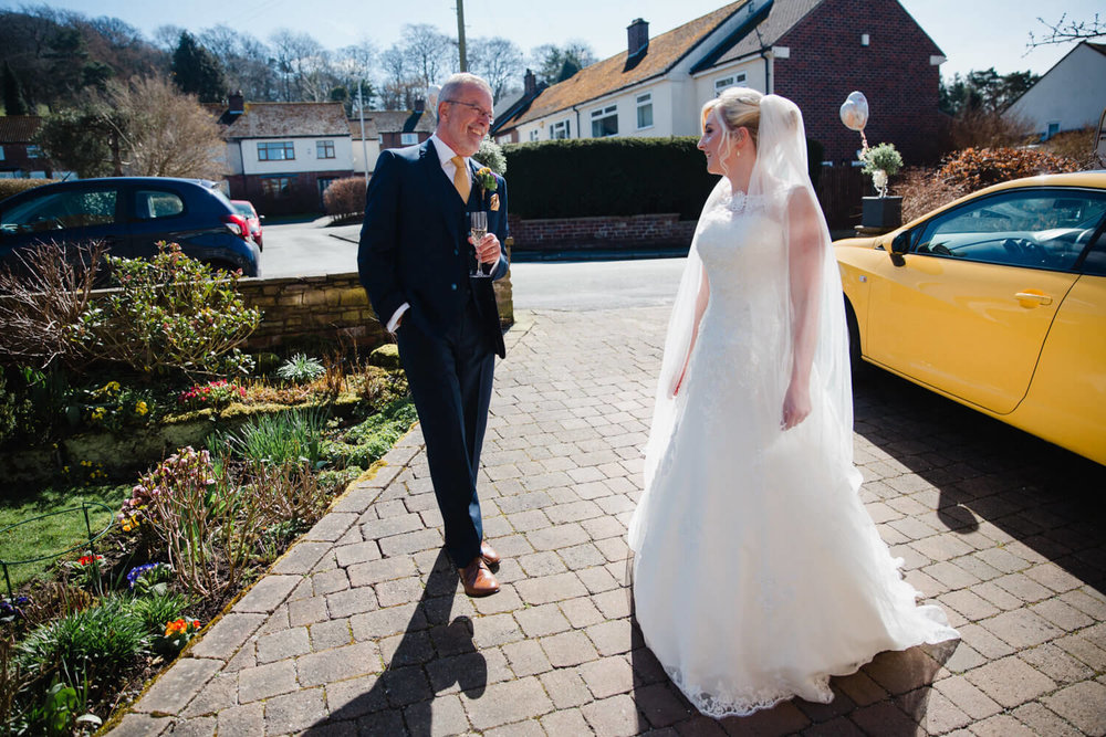 bride and father at front of house waiting for wedding car